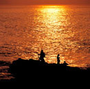 Three persons taking photograph of sea