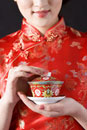 Woman in Cheongsam holding cup of tea