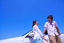 Young couple standing near the car together and smiling