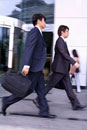 Two businessmen holding briefcase and walking together