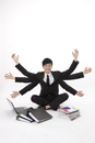 Businessman with multiple arms sitting among laptop, file fo