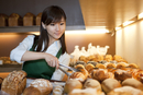 Female baker choosing bread to put into a tray