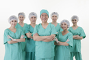 Healthcare workers smiling at the camera with hands on chest