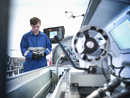 Apprentice engineer holding steel component with lathe in engineering factory