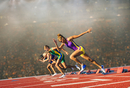 Four female athletes on athletics track, leaving starting blocks