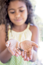 Girl holding small reptile on palm of hands, focus on foreground