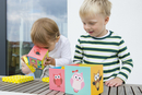 Boy and female toddler playing with owl building blocks on patio