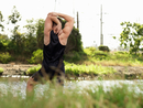 Young man exercising beside river, stretching arms, rear view
