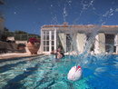 Boy throwing ball in outdoor swimming pool