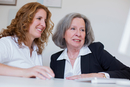 Senior woman and mature woman at desk using computer smiling