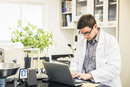 Scientist typing on laptop in laboratory at plant growth research facility