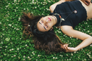 High angle view of woman with nose ring lying on clover covered grass, eyes closed