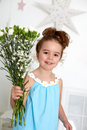Girl with carnations against white wall with stars