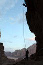 Two silhouetted people rappelling down rock face, Wadi Rum, Jordan