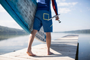 Waist down view of young man carrying paddleboard along pier, lake Pilsensee, Germany