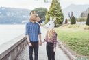 Couple wearing horse and rabbit masks holding hands, Lake Como, Italy
