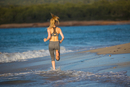 Young woman running through surf, rear view