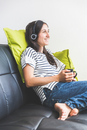 Woman sitting on sofa wearing headphones holding coffee cup smiling