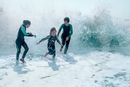 Family wearing wet suits running from waves