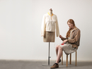 Young female fashion designer sitting on stool pinning blouse on dressmaker
