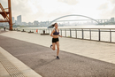 Woman jogging on riverbank in urban area, South Bund, Shanghai, China