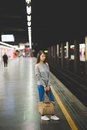Young woman waiting on edge of railway platform at night