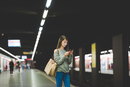 Young woman using smartphone  on railway platform at night
