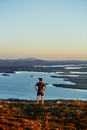 Man looking out to lake on cliff top at sunset, Keimiotunturi, Lapland, Finland