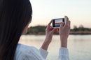Over shoulder view of young woman photographing river at dusk, Beijing, China