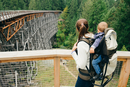 Young woman carrying son on back, rear view, Kinsol Trestle Bridge, British Columbia, Canada