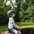 Side view of boy horse riding