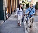 Business man and woman walking in street, man pushing bike, smiling