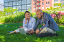 Businessman and woman sitting outdoors on grass, using laptop