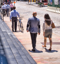 Business people walking along street, mature man pushing bike, rear view