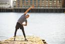 Man stretching on pier, Wapping, London, UK