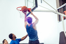 Male basketball player aiming ball for hoop in basketball game