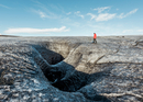 Male tourist walking by glacial crevice, South Iceland