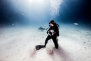 Underwater view of female underwater photographer, looking back from seabed