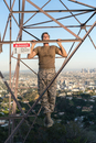 Soldier wearing combat clothing doing chin ups on electricity pylon, Runyon Canyon, Los Angeles, California, USA