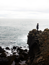 Woman standing on cliff edge, looking at view, Iceland
