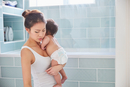 Woman carrying baby daughter in bathroom