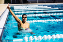 Swimmer in water in pool gesturing triumph