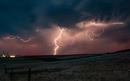 Forked lightning in orange sky over rural area, Grant, Nebraska, United States, North America
