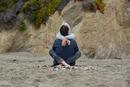 Mature couple sitting on beach cross legged, rear view