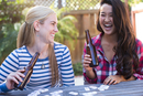 Two young women drinking beer playing dominos