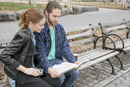 Couple map-reading on park bench, New York, New York, USA