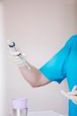 Hands of dental nurse wearing protective gloves holding syringe