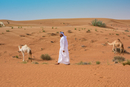 Middle eastern man wearing traditional clothes walking past camels in desert, Dubai, United Arab Emirates