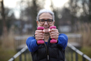Woman wearing glasses holding pink dumbbells looking at camera smiling