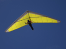 Low angle view of a person hang-gliding against clear blue sky